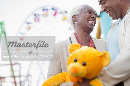Senior couple with teddy bear hugging at amusement park