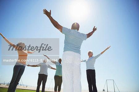 Seniors practicing yoga under sunny blue sky