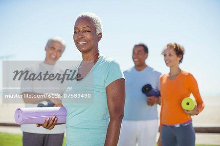 Portrait of confident senior woman with yoga mat in park