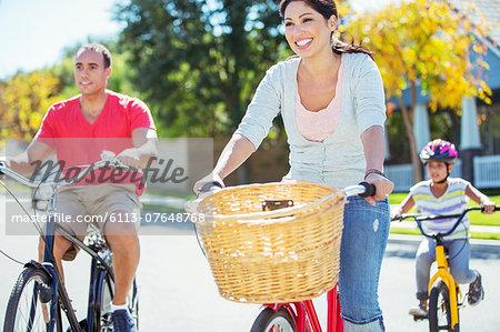 Happy family riding bikes on sunny street