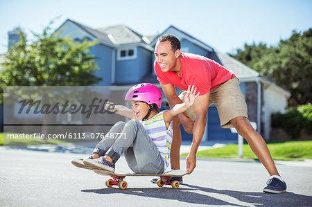 Father pushing daughter on skateboard