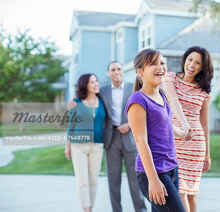 Multi-generation family walking outside house