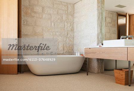 Stone wall behind soaking tub in modern bathroom