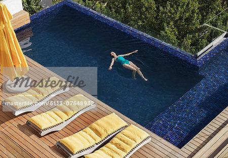 Woman floating in luxury swimming pool