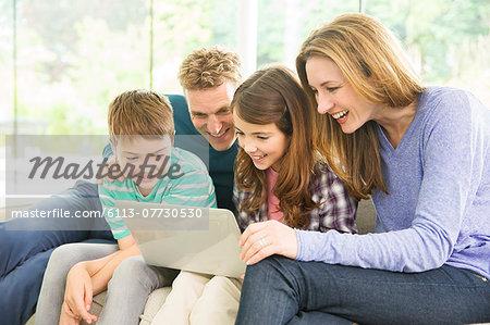 Family using laptop in living room
