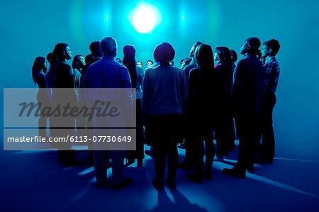 Crowd standing around bright light