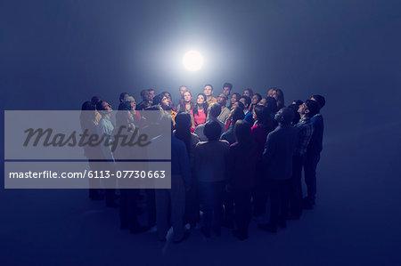 Diverse crowd around bright light