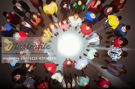 Diverse crowd standing around bright light