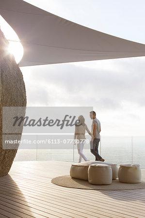 Couple walking on modern balcony