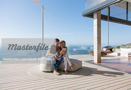 Couple using digital tablet on modern balcony