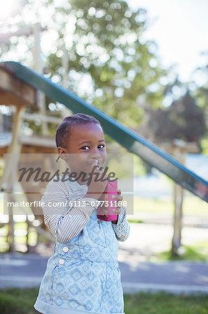 Girl drinking juice box at playground
