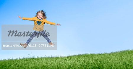 Girl jumping for joy on grassy hill