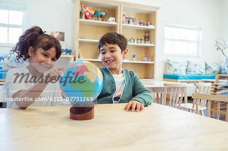 Students examining globe in classroom