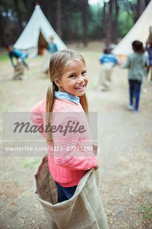 Girl smiling in sack at campsite