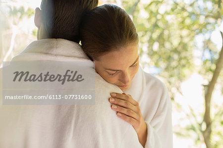 Couple in bathrobes hugging