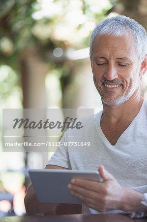 Man using digital tablet at table