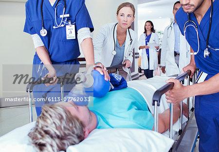 Doctors and nurses wheeling patient down hospital hallway