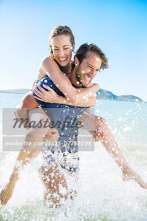 Woman riding piggy back on boyfriend in water
