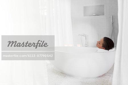 Woman relaxing in bath in modern bathroom