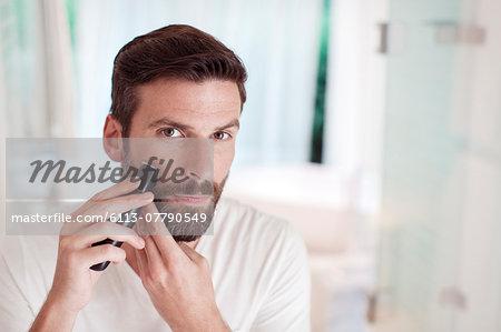 Man trimming beard in bathroom mirror