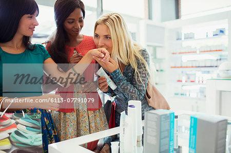 Women smelling perfume in drugstore