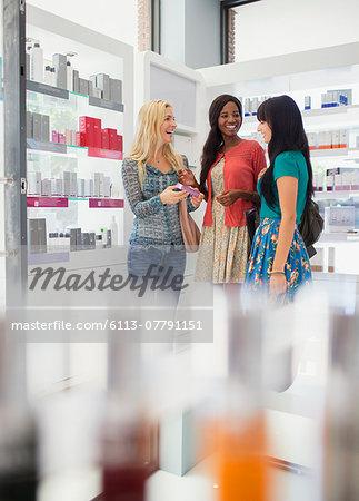 Women examining skincare product in drugstore