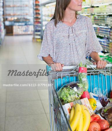 Woman pushing full shopping cart in grocery store
