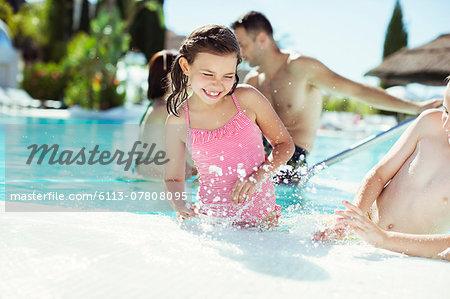 Happy children splashing water in swimming pool