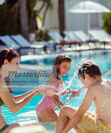 Family with two children splashing water in resort swimming pool