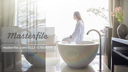 Woman wearing white bathrobe, sitting on edge of bathtub and looking through window