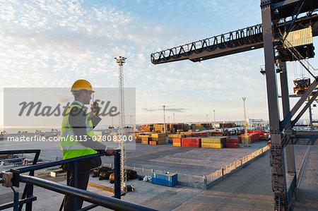 Worker using walkie-talkie near crane
