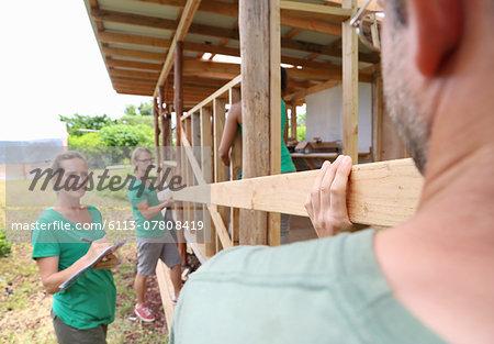 People building wooden house frame together
