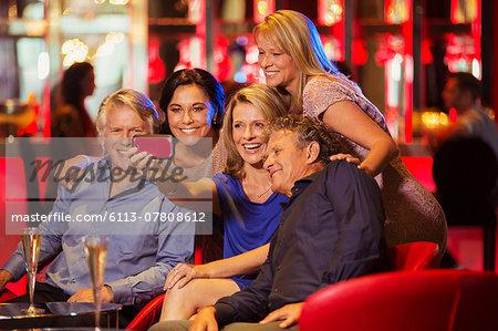 Group of mature friends taking selfie in nightclub