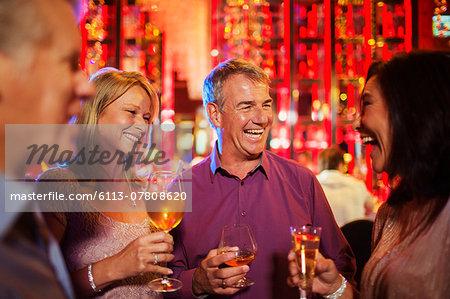 Mature men and women enjoying drinks in nightclub