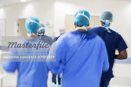Blurred motion of surgeons walking towards hospital