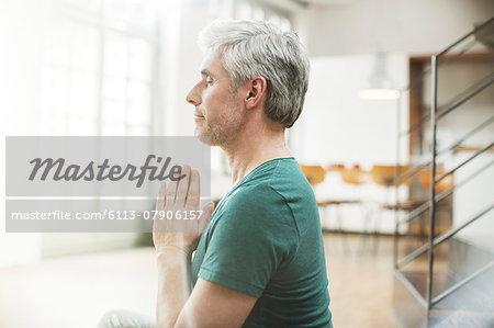 Older man meditating indoors
