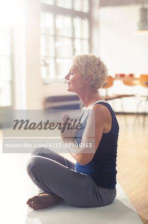 Older woman meditating on exercise mat