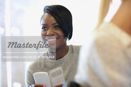 Smiling university student using smartphone at seminar