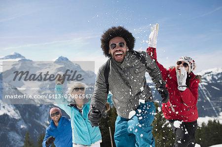 Friends enjoying snowball fight at mountain