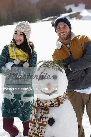 Portrait of couple with snowman