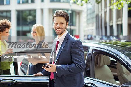 Businessman smiling outside car