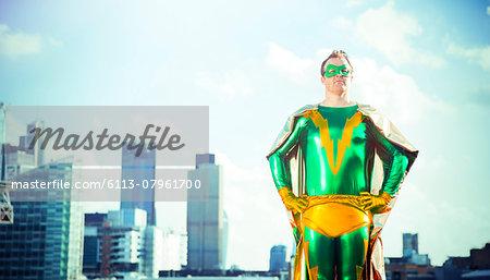 Superhero standing near city skyline - Stock Photo - Masterfile