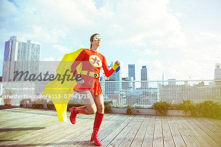 Superhero running on city rooftop