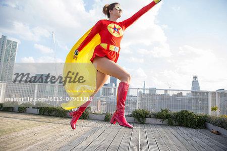 Superhero jumping on city rooftop