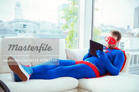 Superhero using digital tablet on living room sofa