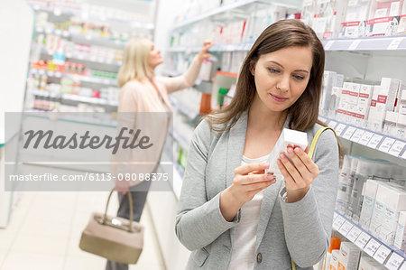 Customer reading label on box in pharmacy