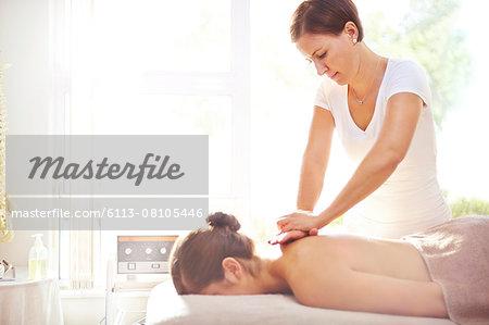 Woman receiving massage by masseuse