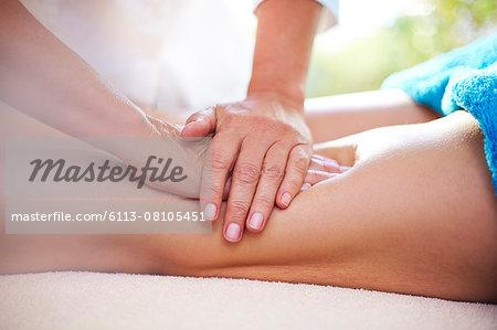 Masseuse rubbing woman's legs