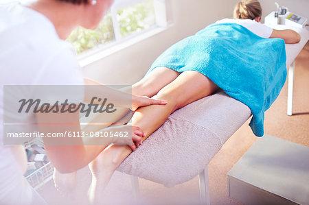 Masseuse massaging woman's leg