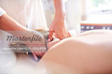 Masseuse massaging woman's neck